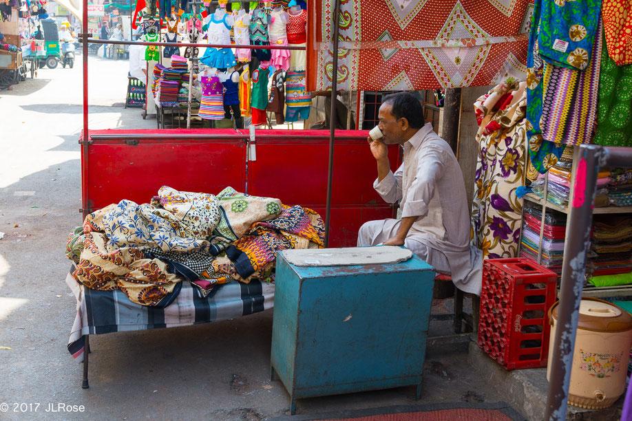 """""""C'est toujours l''heure du thé"""". Marchand de fripes dans la vieille ville d'Ahmedabad (Gujarat / Inde)."""
