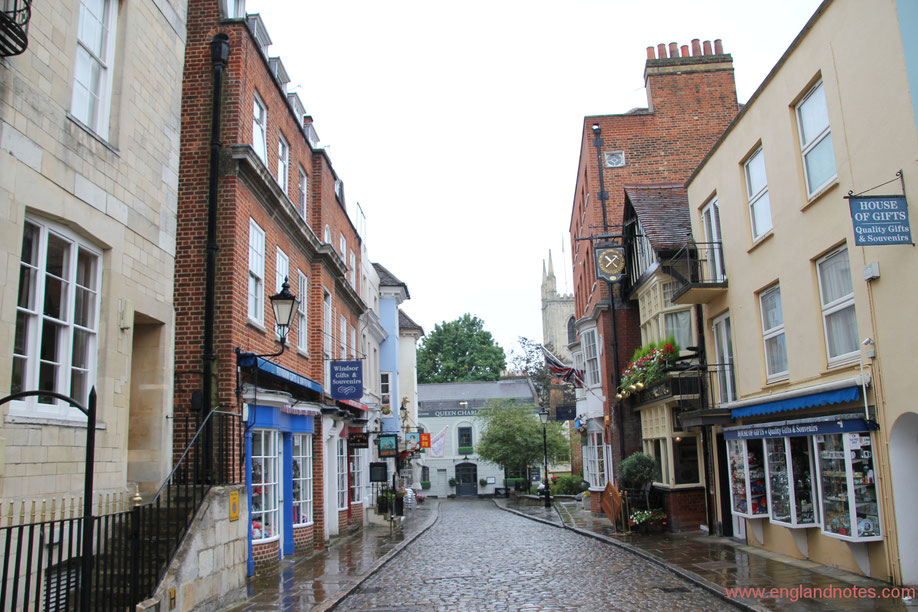 Blick auf eine der historischen Straßen mit Kopfsteinpflaster, Souvenirläden, Restaurants und Cafés in Windsor, Berkshire, England.