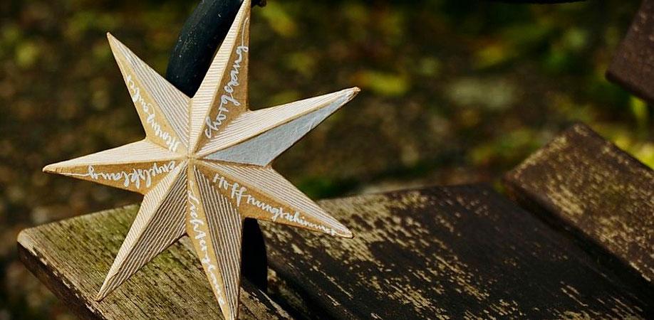 Ein Pappstern (angemalt mit weißen Streifen und Schriftzügen) ist an einer Parkbank befestigt. (Foto: pixabay)