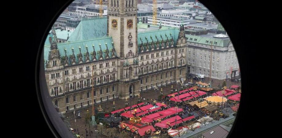 Wie aus einem Fernrohr sieht man das Hamburger Rathaus, vor dem sich kleine Weihnachtsmarktbuden mit rotem Dach befinden.