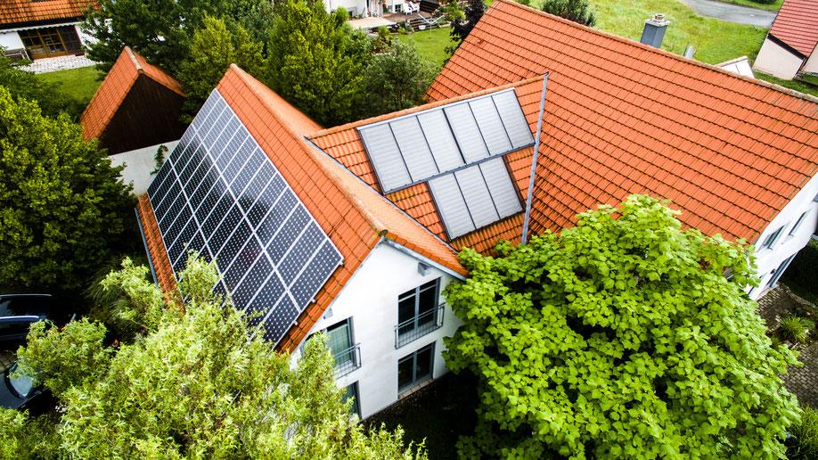 Auf der linken Seite befinden sich Photovoltaikmodule zur Stromproduktion und in der Mitte Solarthermie Kollektoren zur Wassererwärmung © iKratos