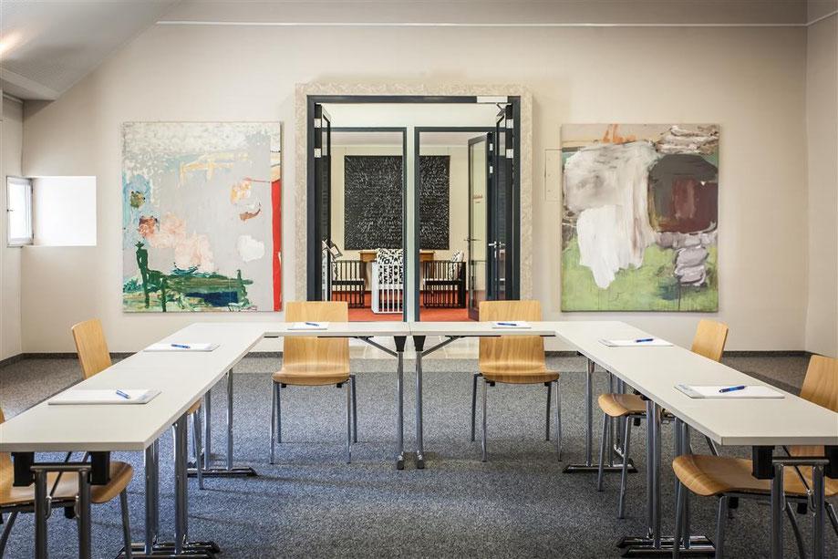 Seminarraum mit Blick zur Bibliothek, Flügeltür geöffnet, heller Raum, Tisch in U-Form aufgestellt, Gemälde von Bach an den Wänden