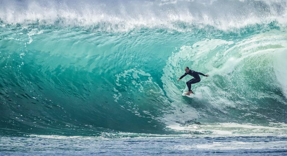Surfista che cavalca una grande onda