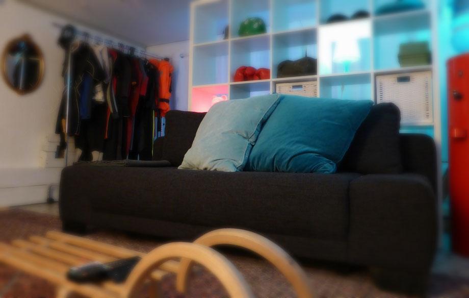 gemütliches Sofa vor Stauraum/ Raumteiler-Regal