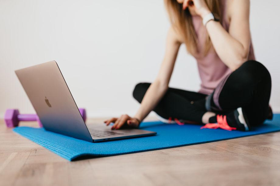 Eine Frau macht Yoga vor dem Laptop