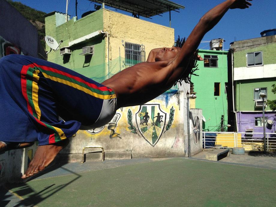 Capoeira Schüler macht einen Salto rückwärts.