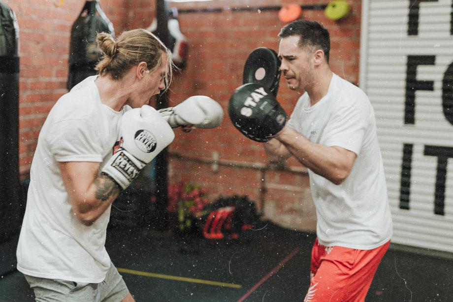 Zwei Männer trainieren Boxen mit Schlagkissen in einem Sportraum.