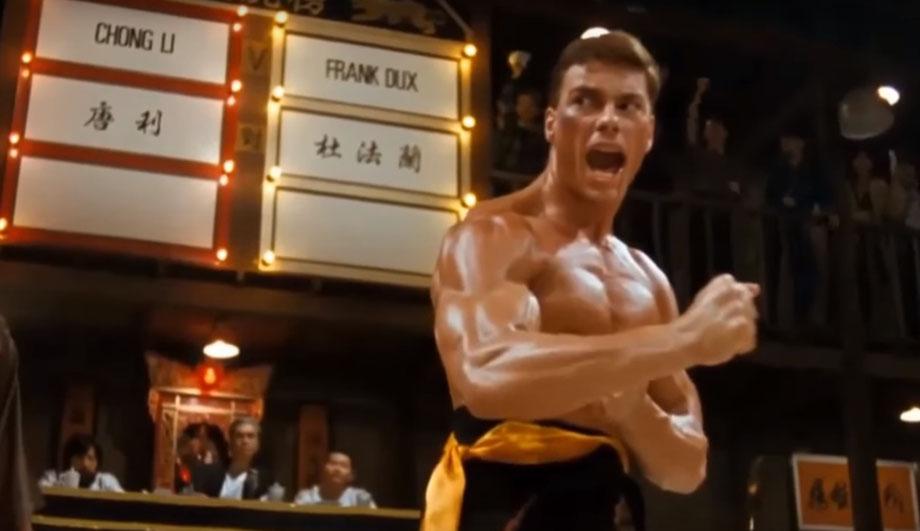 Szene aus dem Endkampf in dem Film Bloodsport. Jean Claude van Damme befindet sich in Kampfposition, im Hintergrund sieht man die Punktetafel und die Kampfrichter.