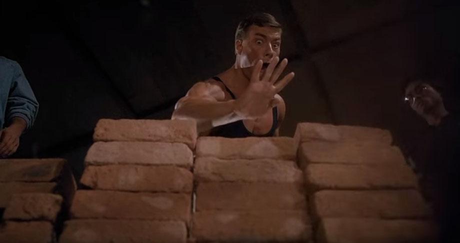Dim Mak - Szene aus dem Film Bloodsport mit Jean Claude van Damme. Jean Claude van Damme schlägt auf einen Stapel aus Ziegelsteinen.
