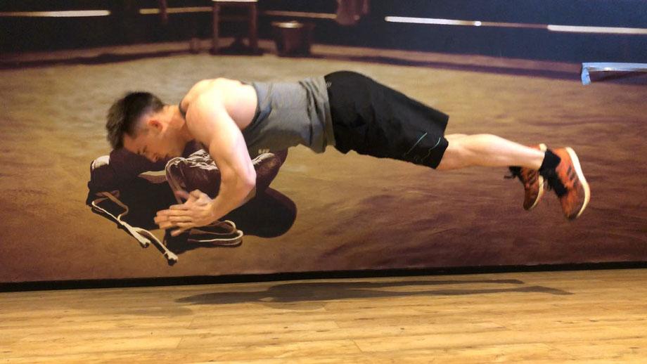 Ein Mann trainiert Liegestütze. Er springt dabei in die Luft und klatscht in die Hände.