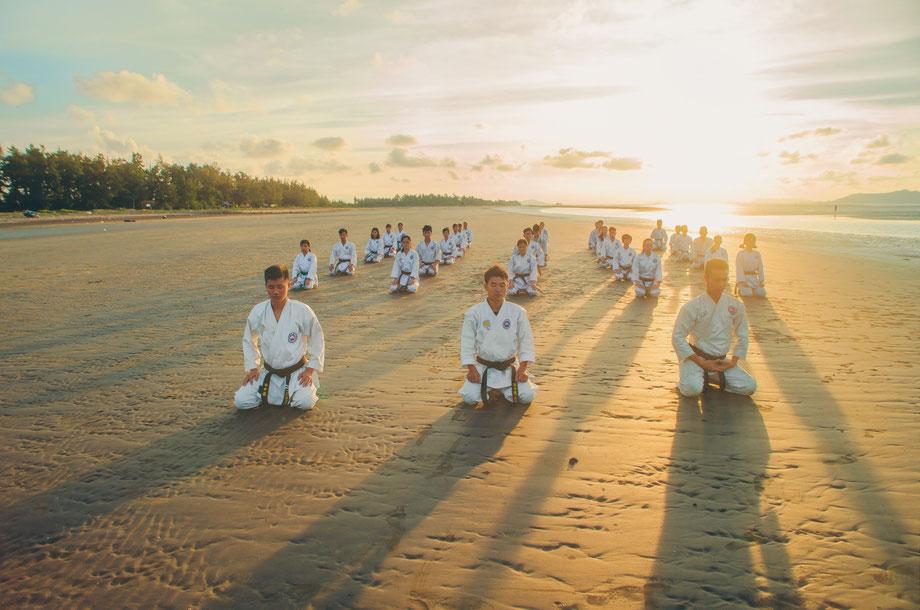 Karate-Meister grüßen gemeinsam an und meditieren vor dem Training am Strand. Im Hintergrund geht die Sonne auf.