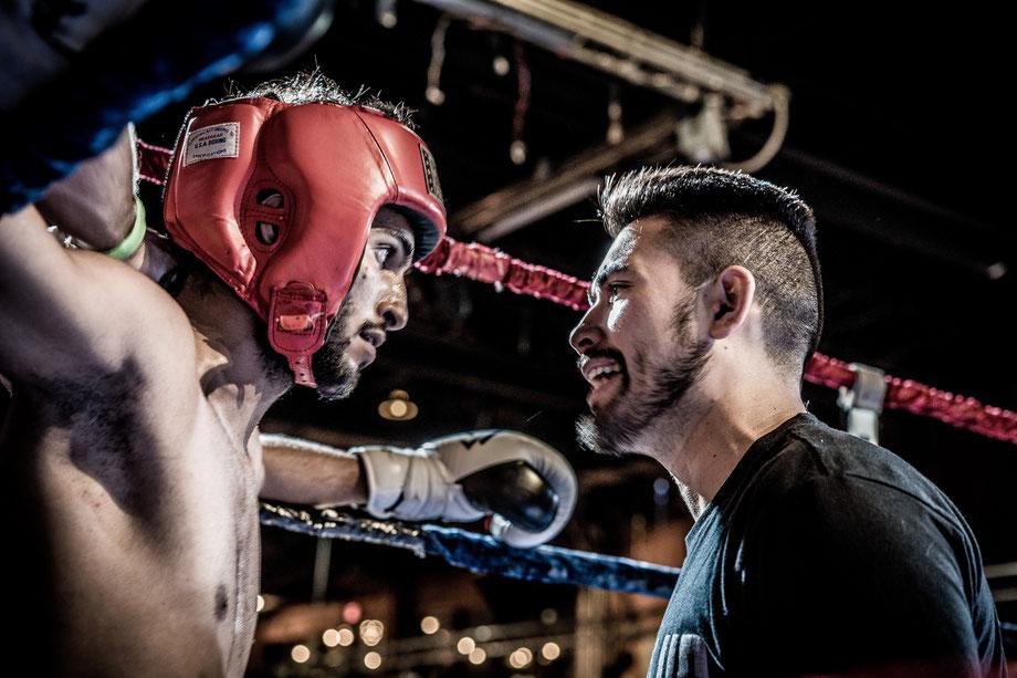 Ein Box-Trainer motiviert seinen Schüler mit dem roten Kopfschutz in der Ringecke.