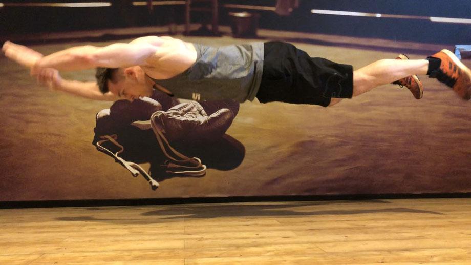 Ein Mann trainiert Liegestütze im Fitnessstudio. Er springt dabei hoch in die Luft und streckt alle vier Gliedmaßen von sich.