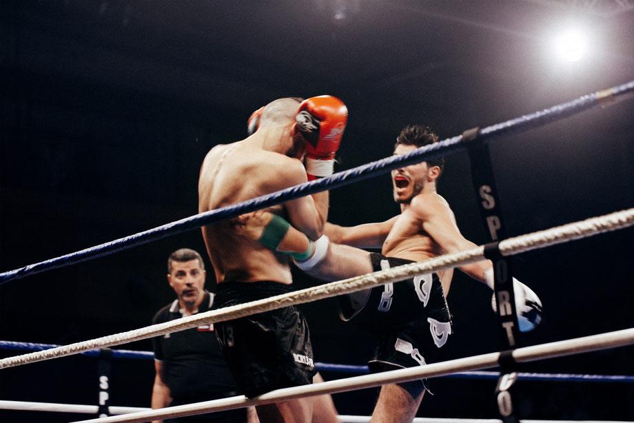 Zwei Muay Thai-Kämpfer kämpfen im Boxring. Der Kämpfer mit den schwarzen Handschuhen tritt den Kämpfer mit den orangen Handschuhen.