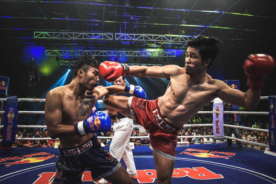 Zwei Muay Thai-Kämpfer im Boxring. Der Kämpfer in der roten Hose tritt den Kämpfer in der schwarzen Hose.