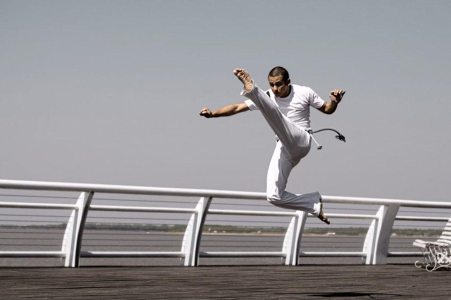 Capoeira Schüler macht einen Sprungtritt nach vorne.