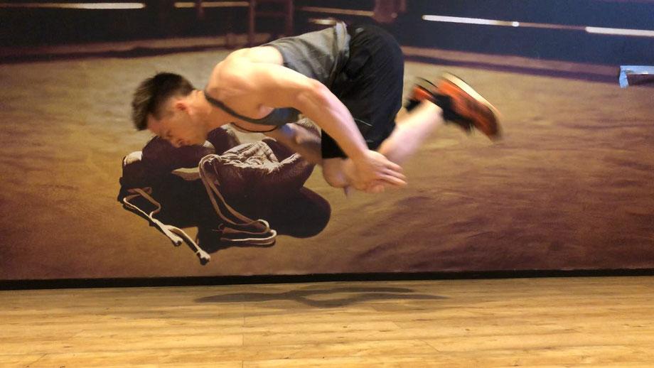 Ein Mann trainiert Liegestütze im Fitnessstudio. Er springt dabei hoch in die Luft und macht sich in der Luft klein, damit er mit den Händen seine Knie berühren kann.