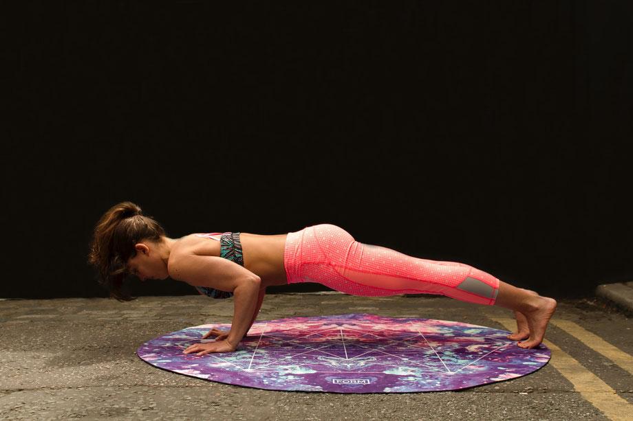 Eine Frau trainiert Liegestütze auf einer Yogamatte.