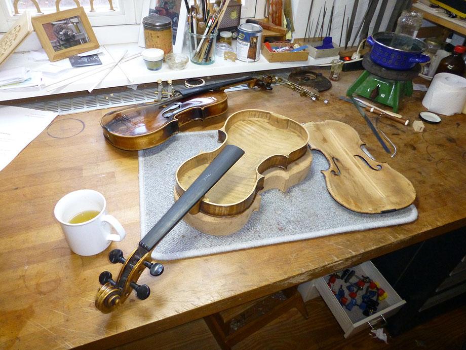 Geige, offen. Auf dem Arbeitstisch der Geigenbauerin