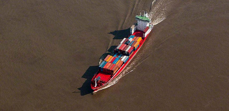 container vessel on elbe river from above. Feeder von englisch to feed, d.h. füttern. im sedimentreichen Wasser