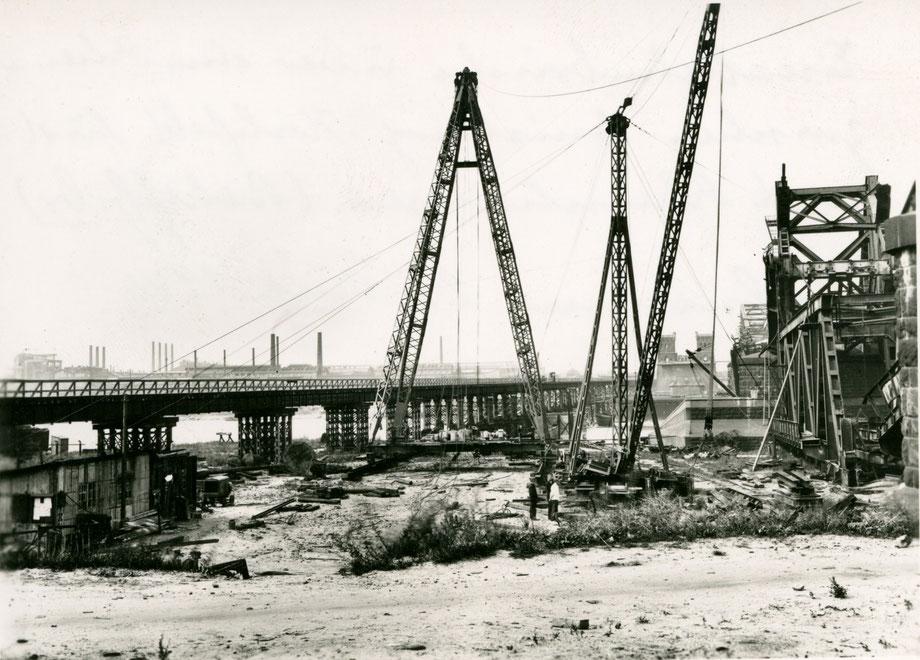 Quelle: Verkehrsmuseum Nürnberg, Die fertige Behelfsbrücke, links im Bildhintergrund Krupp-Rheinhausen. Rechts im Bild, Abbau der gesprengten Eisenbahnbrücke. Aufnahme-Datum: Juni 1945