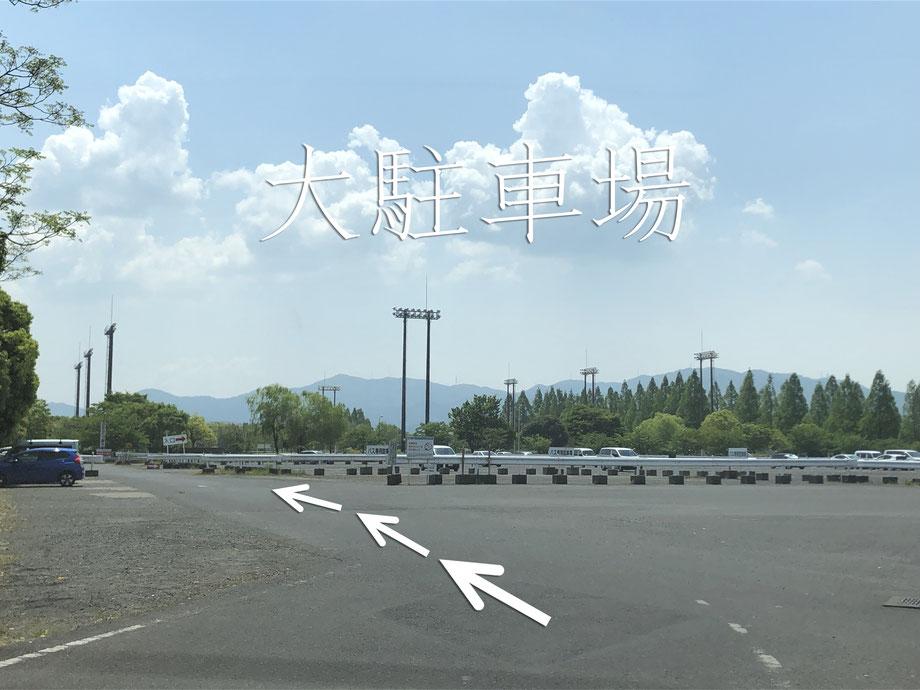 突き当たりまで来ると、右手に大駐車場が現れます。大駐車場を矢印の方向に進む