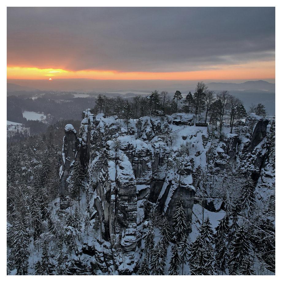 first sunlight - die Sonne erscheint fern hinter der Felsenburg Neurathen