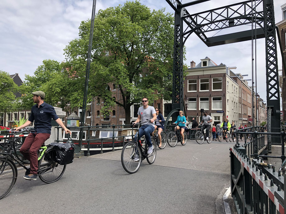 A bike tour group crossing an old bridge in Amsterdam