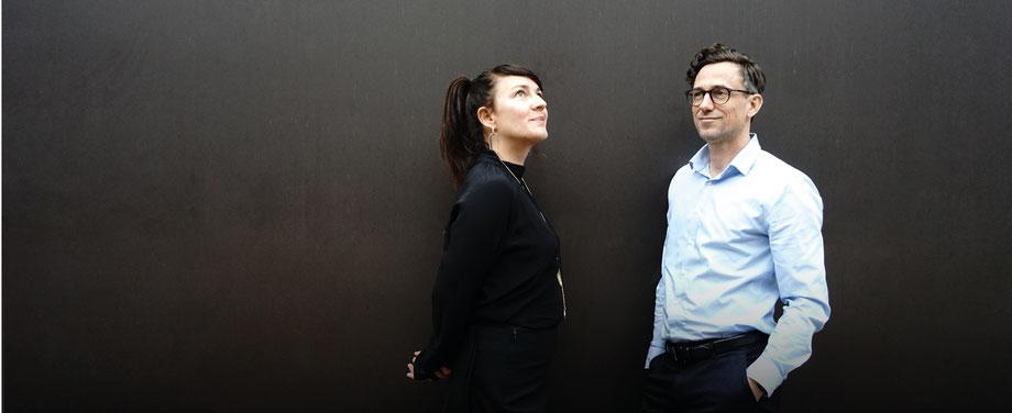 Das Bild zeigt Anne-Maria Wende und Henrik Wärnke in lockerer Haltung vor einem dunklen Hintergrund.  komjunik - Marketingagentur und Werbeagentur aus Magdeburg