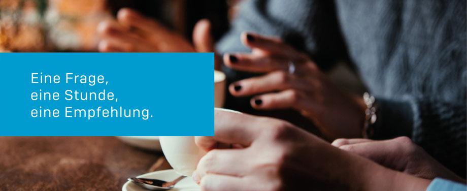 Das Bild zeigt eine Besprechungssituation mit den Händen einer Frau und eines Mannes in blauer Kleidung und dazu zwei Tassen Kaffee.  Im hellblauen Kasten links steht geschrieben: Eine Frage, eine Stunde, eine Empfehlung.