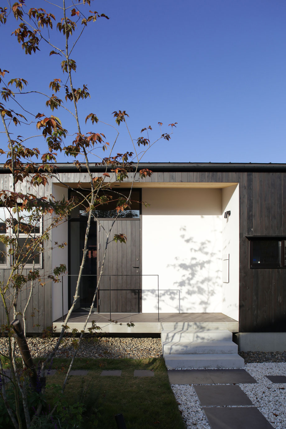 新潟県上越市の設計事務所、中島智幸建築設計一級建築士事務所が設計監理を行った「上越の家 -暮らしを守る平屋」です。外壁の杉板と白壁と青空のコントラストがとても綺麗な平屋です。大判(600各)タイルの玄関アプローチは、訪れる人々を優しく誘導します。