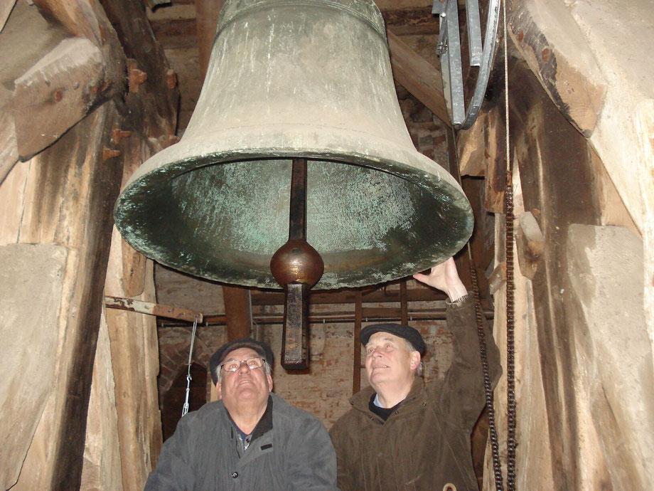 Dieter Kölpien und Gernot Moeller (vl) in Güstrow unterwegs. Hier bei der Betrachtung der größten Glocke im alten Kirchenkreis Güstrow von 1425. Die Glocke gehört zu den ältesten Denkmalen Güstrows.