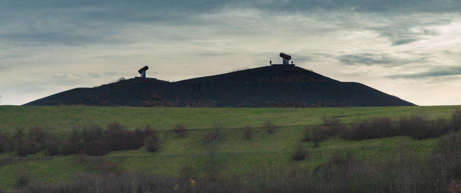 """Blick von unten auf die markanten Gipfel der Halde. Schön der Kontrast zwischen grünem Gras und schwarzer """"Kohle"""""""
