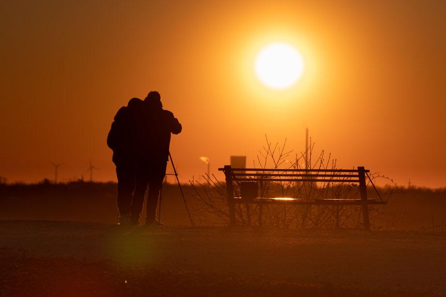 Die Sonne sinkt tiefer. Von Menschen und Gebäuden sind gegen das Licht nur noch die Umrisse zu sehen. Die Sonne taucht den Horizont in ein tiefes Orange