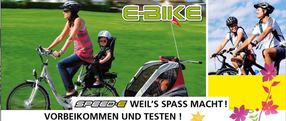 Eine Frau am E-Bike fahren in der Schweiz mit zwei Kindern, Kindersitz und Anhänger am Elektrovelo
