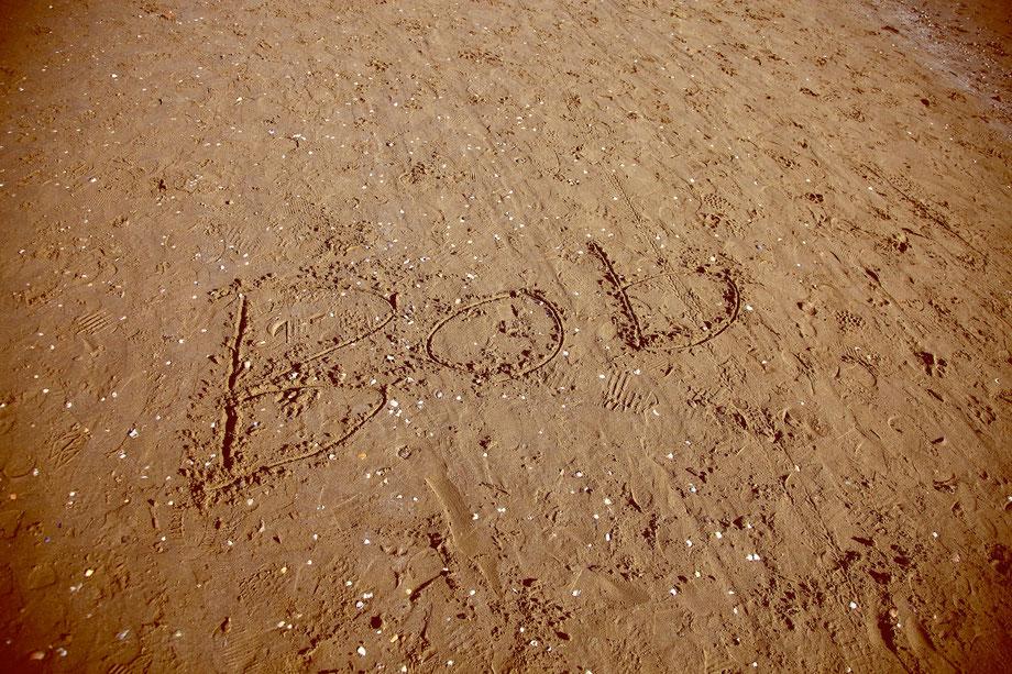 Foto geschriebener Text im Sand eines Strandes. Lido.