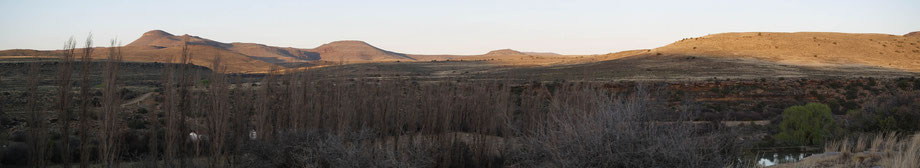 View over the farmland, setting sun in my back, lots of hills, trees, a lake and bush land.