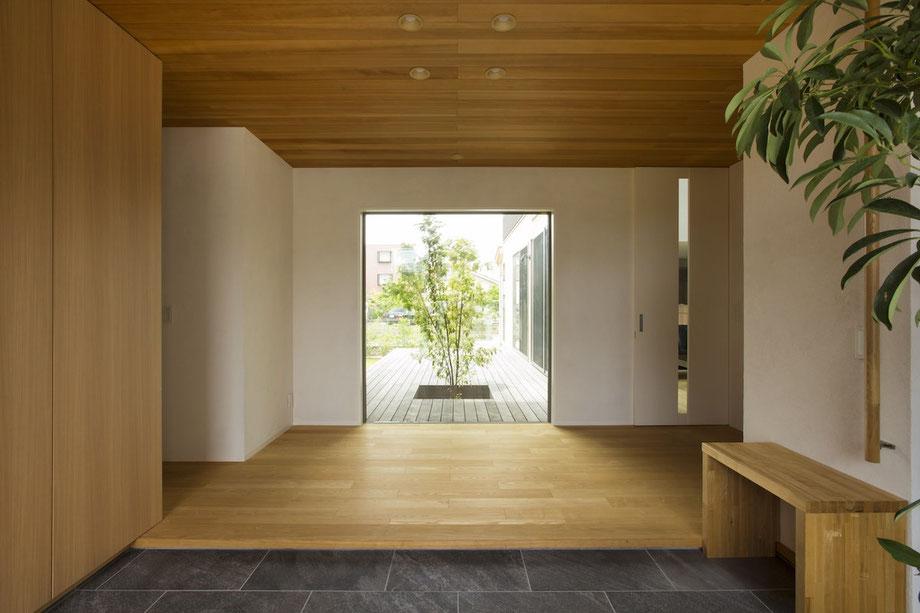 玄関入った正面に中庭の木を眺めるピクチャーウィンドウを設置しました。外に目を向けることで内と外を繋げています。玄関