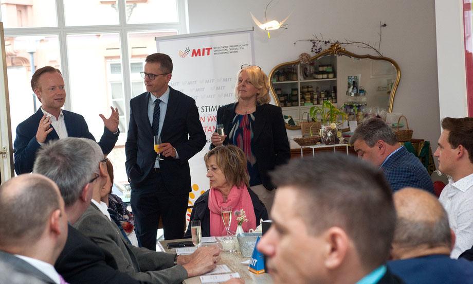 Der Bundestagsabgeordnete Jan Metzler, MIT Bundesvorsitzender Carsten Linnemann und die Wormser MIT Vorsitzende Iris Muth (stehend, von links) begrüßen zahlreiche Gäste.