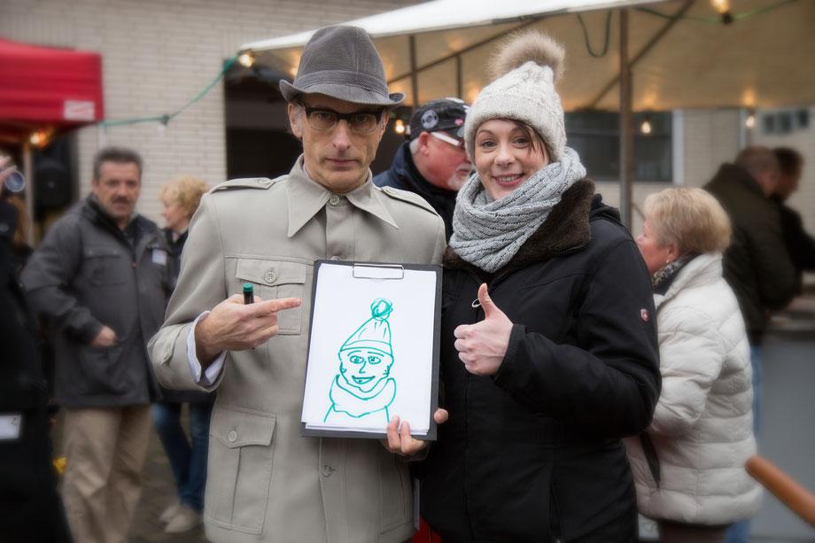 Künstler mit Zeichnung und Gästen für Ihrem mobilen Weihnachtsmarkt