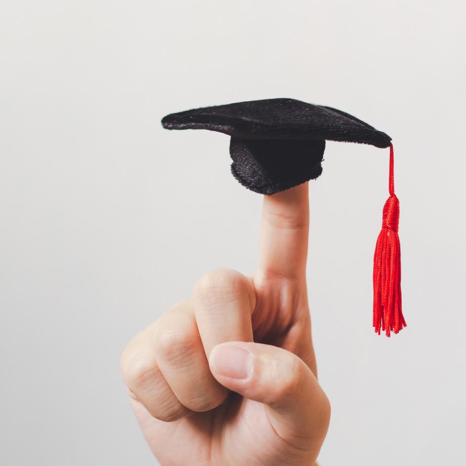 Hand mit ausgestrecktem Zeigefinger, auf dem ein Fingerhut sitzt, der einen Studienhut darstellt