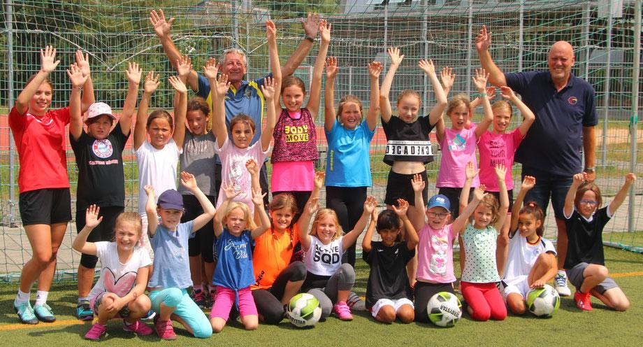"""19 Mädchen nahmen am """"Tag des Mädchenfußballs"""" teil; auf dem Foto neben den Teilnehmerinnen: die Trainer Dilay Can (links) und Heiner Bosse (rechts) sowie Peter Oberndorfer vom Förderverein (Mitte)"""