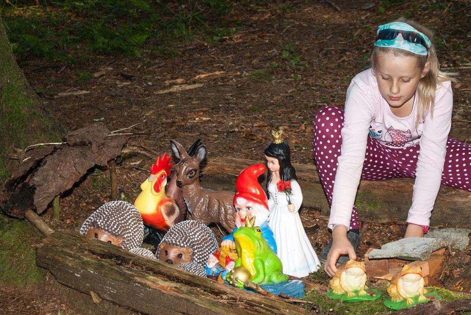 Mädchen spielt mit Märchenfiguren im Zwergenwald am Biobauernhof Stadler