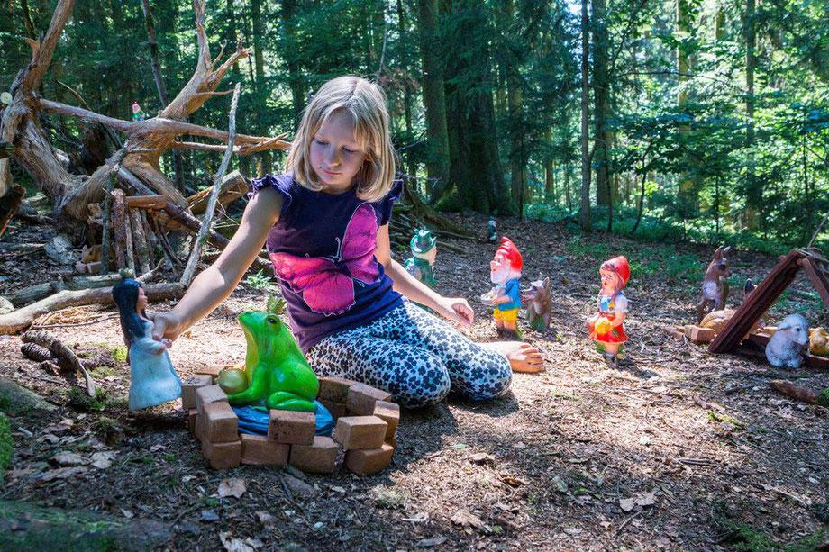 Mädchen spielt mit Märchenfiguren im Zwergen-wald am Biobauernhof Stadler