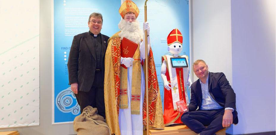 Verkleidet als Nikolaus wird Roboter Pepper den Besuchern des HNF eine kleine Freude machen. Von Links: Monsignore Georg Austen, Bischof Nikolaus, Roboter Pepper und Jochen Viehoff. © Jan Braun/HNF