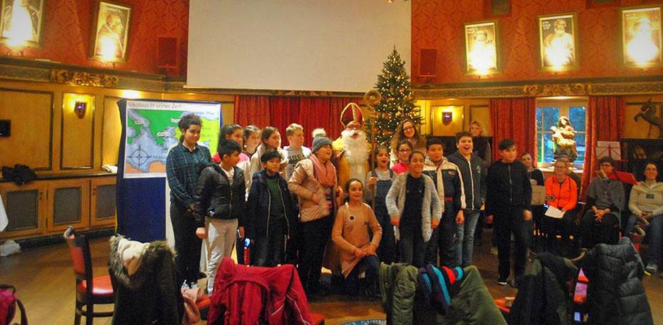 Mädchen und Jungen stehen neben dem Nikolaus und singen gemeinsam ein Lied, rechts im Hintergrund sitzen die Musikanten