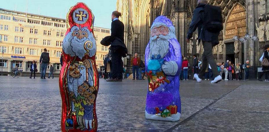 Im Vordergrund steht der rotgekleidete (Schoko)Nikolaus und rechts daneben der lilafarbene (Schoko)Weihnachtsmann. Im Hintergrund sieht man den Kölner Dom, an dem Leute vorbeigehen.
