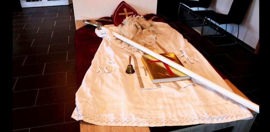 Auf einem Holztisch liegt das weiße Gewand des Nikolaus', sowie sein roter Bischofsumhang, die Mitra, der Bischofsstab-