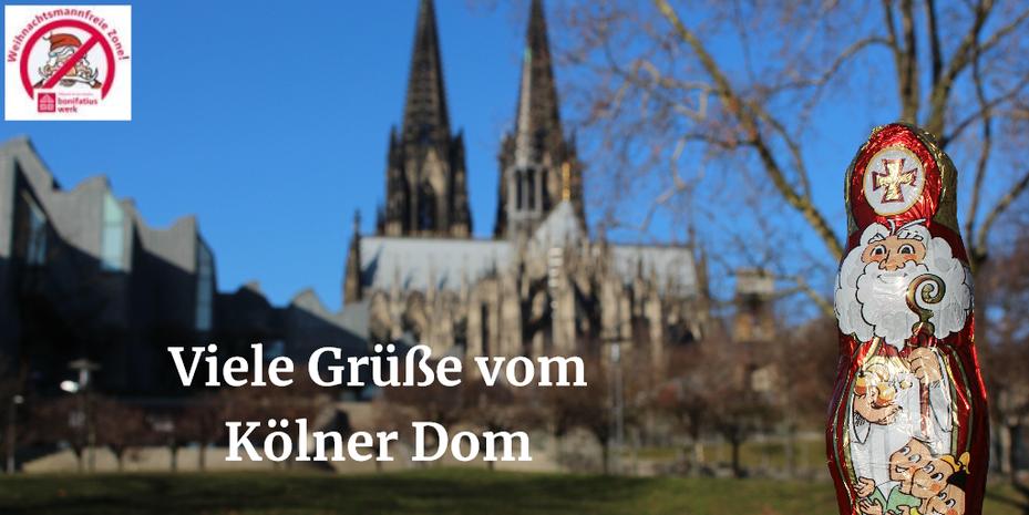 Der Schokonikolaus steht auf einer Mauer. Im Hintergrund ist der Kölner Dom mit seinen zwei markanten Spitzen zu sehen.