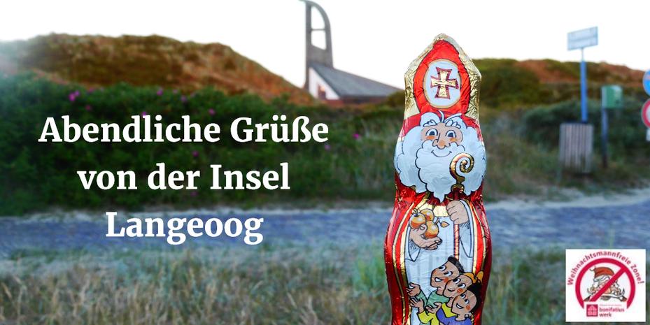 Der Schokonikolaus steht vor der St.-Nikolaus-Kirche auf Langeoog, die von Sanddünen umgeben ist.